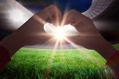 picture of football pitch  - Woman making heart shape with hands against football pitch in large stadium - JPG