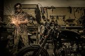 stock photo of rockabilly  - Mechanic doing lathe works in motorcycle customs garage  - JPG