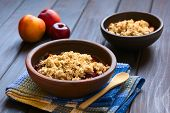 image of crisps  - Two rustic bowls filled with baked plum and nectarine crumble or crisp photographed on dark wood with natural light  - JPG