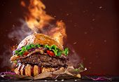 stock photo of hamburger-steak  - Delicious hamburger with fire flames on wooden background - JPG