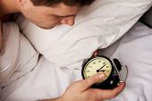 pic of late 20s  - Man lying on the bed with alarm clock - JPG