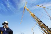 stock photo of construction crane  - construction worker talking to crane driver inside building site - JPG