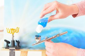 image of airbrush  - Adding blue paint to a professional airbrush - JPG