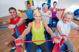 picture of senior class  - Portrait of happy men and women on fitness balls exercising with resistance bands in gym class - JPG