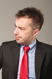 picture of disapproval  - Side view picture of a young business man looking to his side while making a disapproving face - JPG
