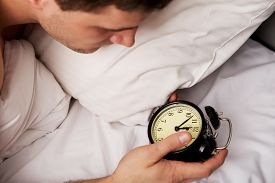 stock photo of early 20s  - Man lying on the bed with alarm clock - JPG