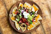 stock photo of nachos  - Homemade Nachos with tortilla chips cheese and guacamole - JPG