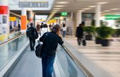 stock photo of mobile-phone  - man on escalator is going to his gate - JPG