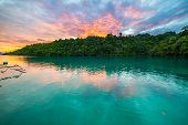 foto of jungle  - Breathtaking colorful sunset on scenic turquoise bay bordered by lush green jungle in the remote Togean (or Togian) Islands upgrowing travel destination in Sulawesi Indonesia. Summer adventures in South East Asia. ** Note: Soft Focus at 100%, best at sma - JPG