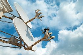 stock photo of antenna  - Satellite antennas searching for a signal over blue sky - JPG