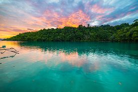 stock photo of south east asia  - Breathtaking colorful sunset on scenic turquoise bay bordered by lush green jungle in the remote Togean (or Togian) Islands upgrowing travel destination in Sulawesi Indonesia. Summer adventures in South East Asia.