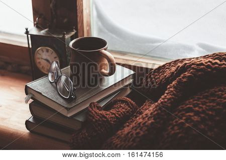 poster of Warm and comfy winter concept. Book, cup of tea and sweater on wooden window sill in old house. Read