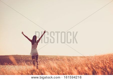 poster of Free woman raising arms to golden sunset. Freedom and success concept. Girl relaxing and enjoying nature with copy space. Toned film effect