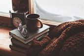 Warm and comfy winter concept. Book, cup of tea and sweater on wooden window sill in old house. Read poster