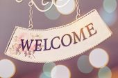 Selective Focus Of Welcome Sign Hanging On Ceiling, Sweet Tone. poster