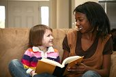stock photo of babysitter  - Beautiful african american woman reading to a 5 year old girl at home - JPG