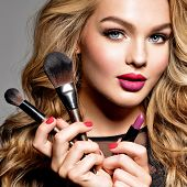 Beautiful woman holds cosmetic tools. Makeup. Beauty concept. Pretty girl with long curly hair.  Fas poster