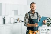 Smiling Handsome Plumber Holding Clipboard And Looking At Camera In Kitchen poster