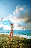young beauty woman stands on sea beach with kerchief