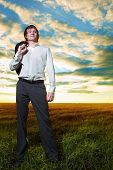 young businessman in field under sky with clouds