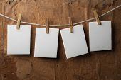 four photo paper attach to rope with clothes pins on paper background