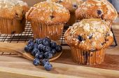 Blueberry Muffin And Spoonful Of Berries On A Wooden Spoon With Muffins On Cooling Rack In Backgroun poster