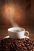 stock photo of cup coffee  - warm cup of coffee on brown background - JPG