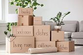 Pile Of Moving Boxes And Household Stuff In Living Room poster