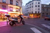 The streets of Paris are still full of activity, lit by neon advertisements, signs and billboards; p