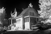 An infra-red photo of a suburban residence with and old pick up truck in the drive way, giving it an