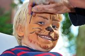 stock photo of face painting  - The face of a young child being made to look like a ferocious lion by a make - JPG