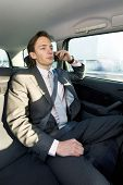 A young businessman making a call in the backseat of a taxi