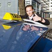 A smiling taxi driver giving a thumbs up while placing his taxi sign on the roof of his car