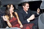 A young couple laughing in the backseat of a car after a night out, smoking cigarettes