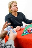 A card player shuffling cards during a poker game with one of his competitors in the background - Se