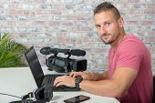A Video Editor With Laptop  And Professional Video Camera poster