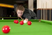 Man, dressed in a black shirt, playing snooker