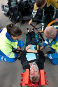 Paramedics and a fireman strapping an injured woman to a stretcher, seen from above