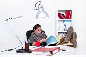 Young woman studying tirelessly, flipping through a folder with her feet on her desk - the backgroun