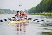 Coxed four rowing team paddling backwards to the start, with concentrated looks in their eyes, in an