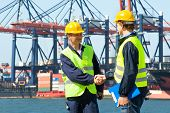 Two dockers shake hands in front of an industrial harbor with cranes and a container ship being unlo