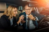 Couple In Formal Wear With Car Key Sitting In New Car For Test Drive poster