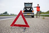 Warning triangle behind a broken down car with a motorist calling for assistance. Focus on the trian