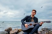 Young Man With Acoustic Guitar Playing And Singing On Beach Surrounded With Rocks On Rainy Day poster