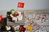 Various National Oriental Sweets, With Paper Flags Of Turkey, Turkish Delight On A Wooden White Brus poster