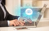 Business woman in homey environment using laptop with  online storage and cloud technology concept poster