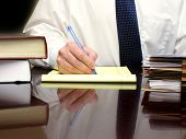Business Man sitting at Desk holding Stift mit Dateien