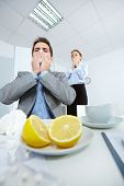 Image of businessman sneezing while his partner on background looking at him with fright in office