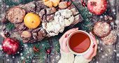 Female Hand A Cup Of Tea. Christmas Cookies Chocolate, Tea, Pomegranate, Tangerines, Nuts, Cocoa Bea poster