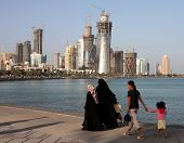 Covered Qatari women with their children and housemaid strolling on the Corniche in Doha, Spring 200